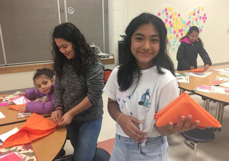 Young girls create crafts out of orange paper