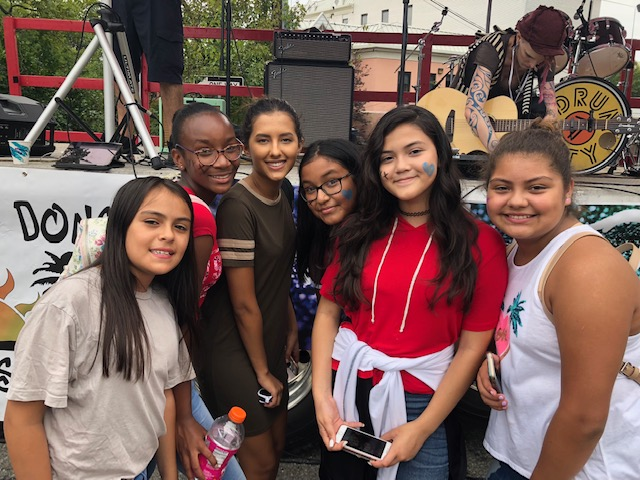 A ground of 6 pre-teen girls, some with face paint, stand outdoors, smiling at the camera, in front of a stage.
